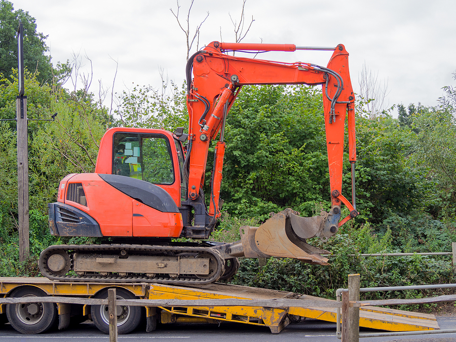small tracked excavator being loaded onto a flatbed transporter