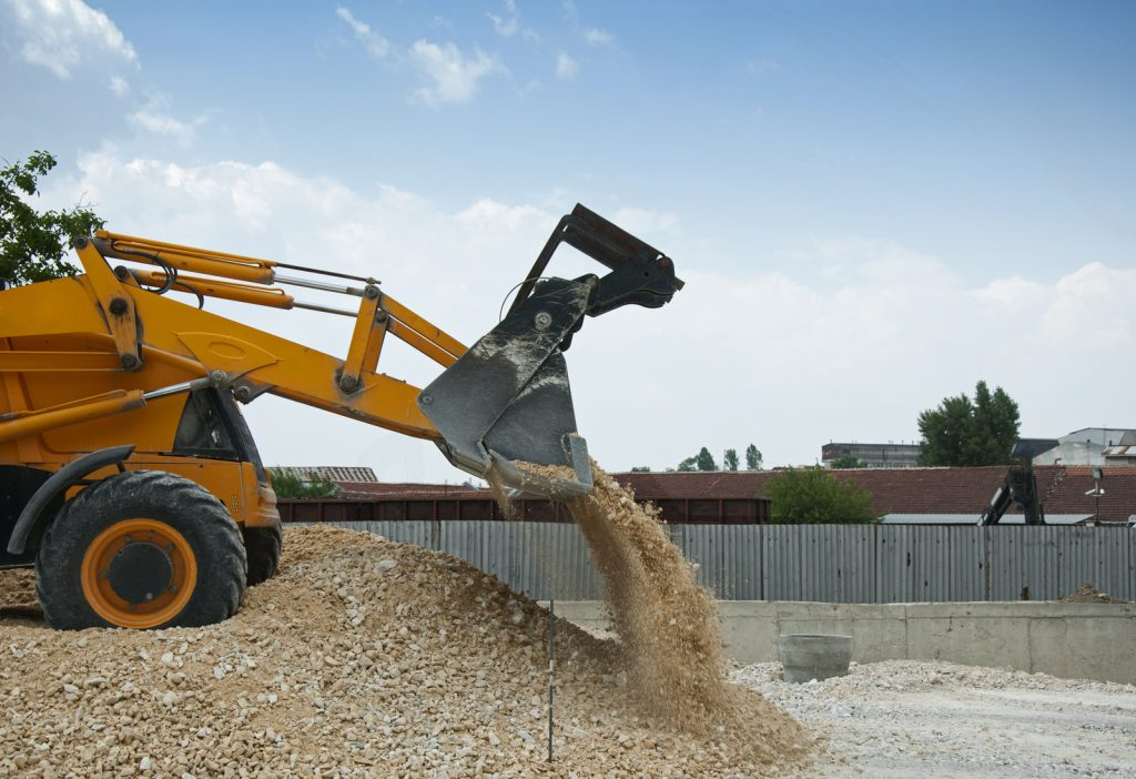 a backhoe truck pouring sand/gravel
